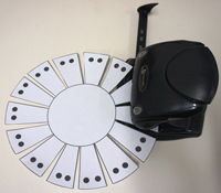 A photograph of a hole-punch placed over black dots on a sample basket template.