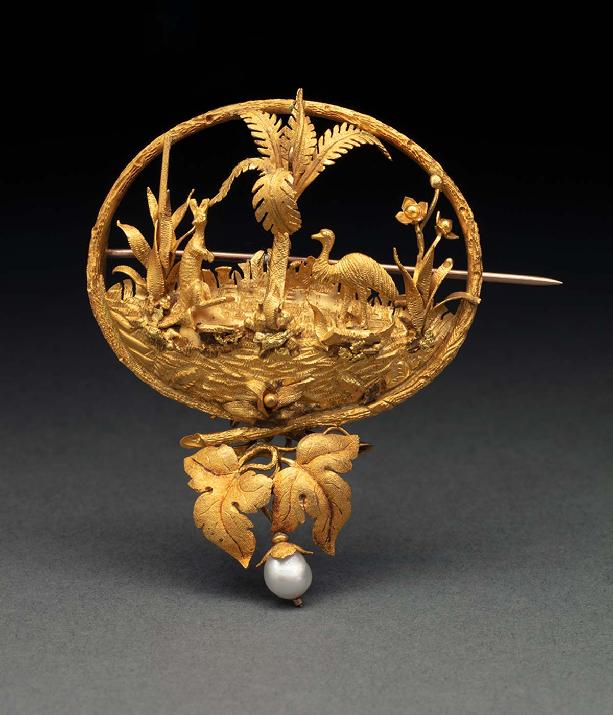 Gold brooch showing a picture of a kangaroo and emu, with a pearl drop at the bottom. - click to view larger image
