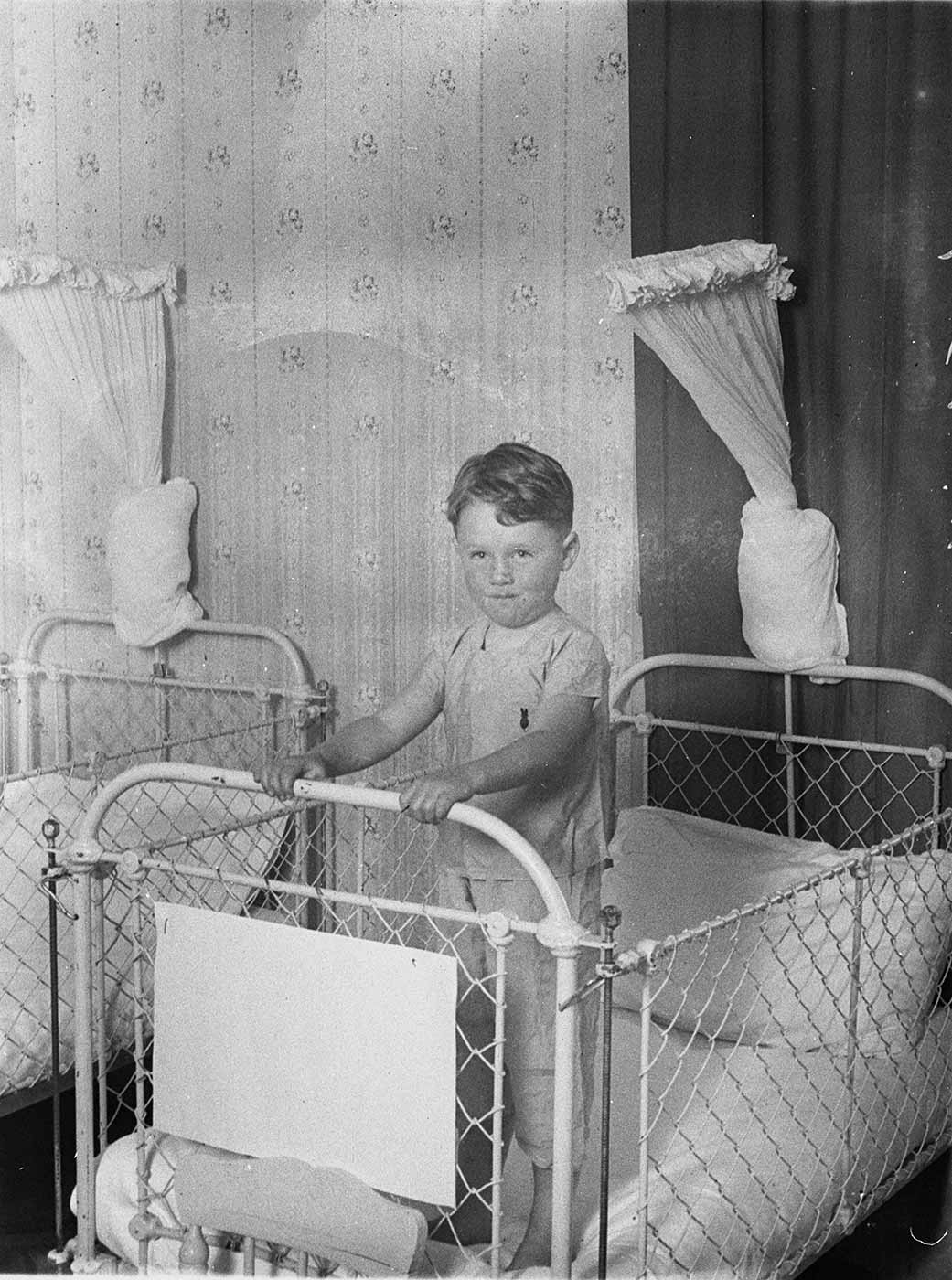 Boy standing in a metal framed cot with wire mesh sides. - click to view larger image