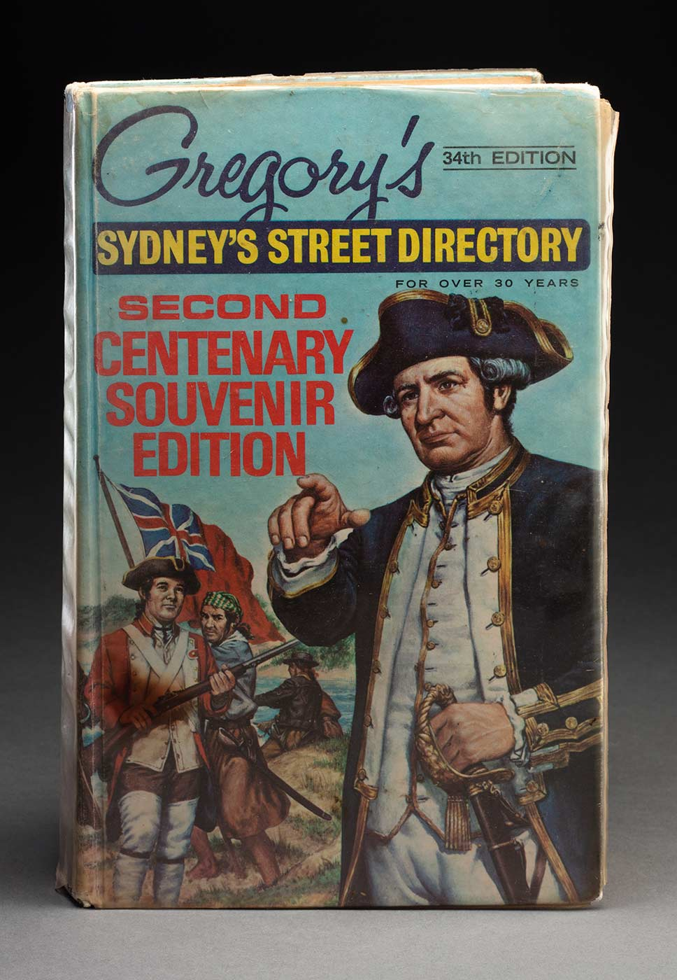 Gregory's 34th edition 'Sydney's Street Directory', second centenary souvenir edition. The front cover features a colour image with Captain Cook in the foreground on the right, and several other men with a flag in the background on the left. The cover has a plastic jacket. - click to view larger image