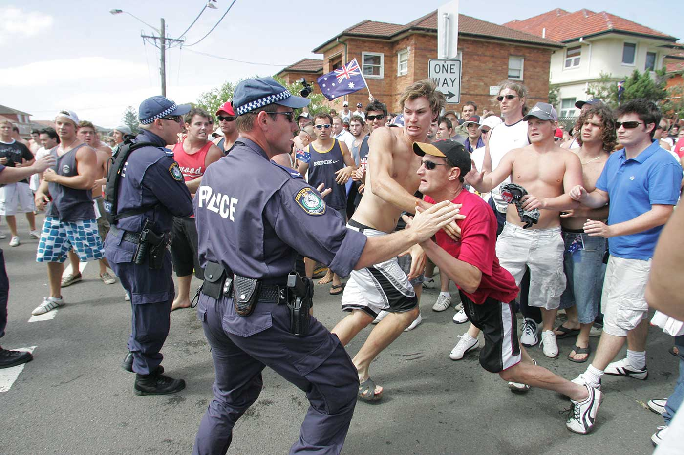 Colour photograph of police trying to hold back a large crowd of angry predominantly young white male protesters on a street.
