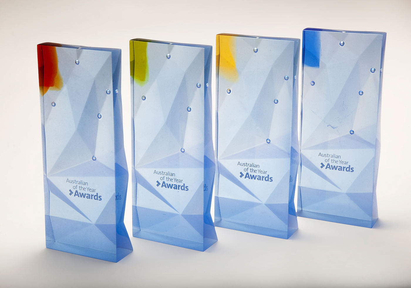 Four largely clear glass trophies with text 'Australian of the Year' and a small coloured glass tab top left. - click to view larger image