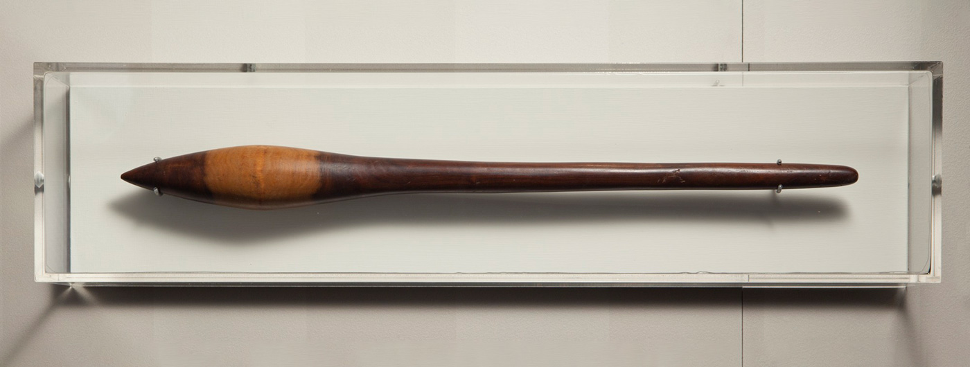 Photograph of a wooden club, mounted on a wall in a perspex display case. - click to view larger image