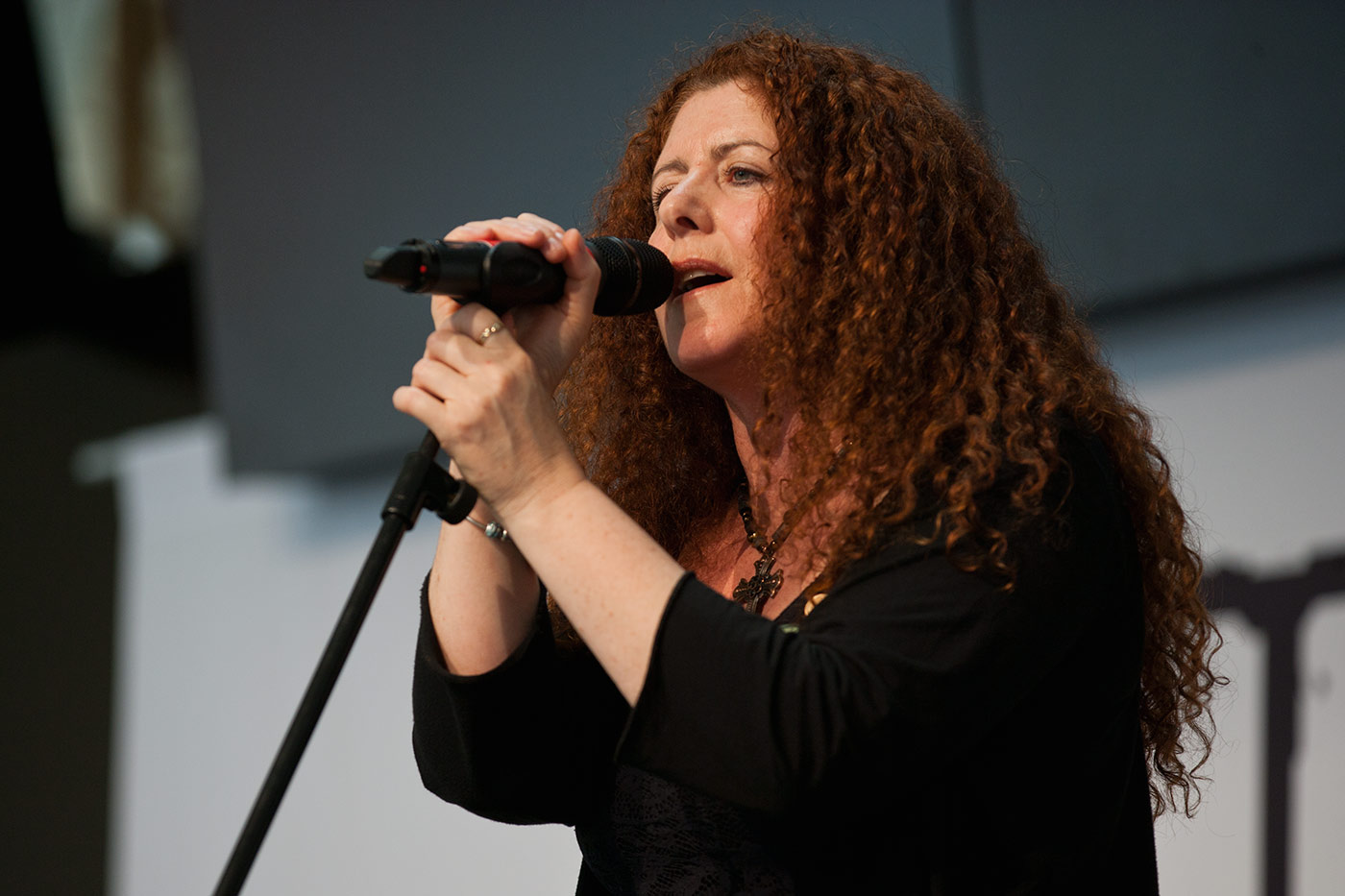 A woman with long flowing red hair is holding a microphone while looking directly at the camera. - click to view larger image