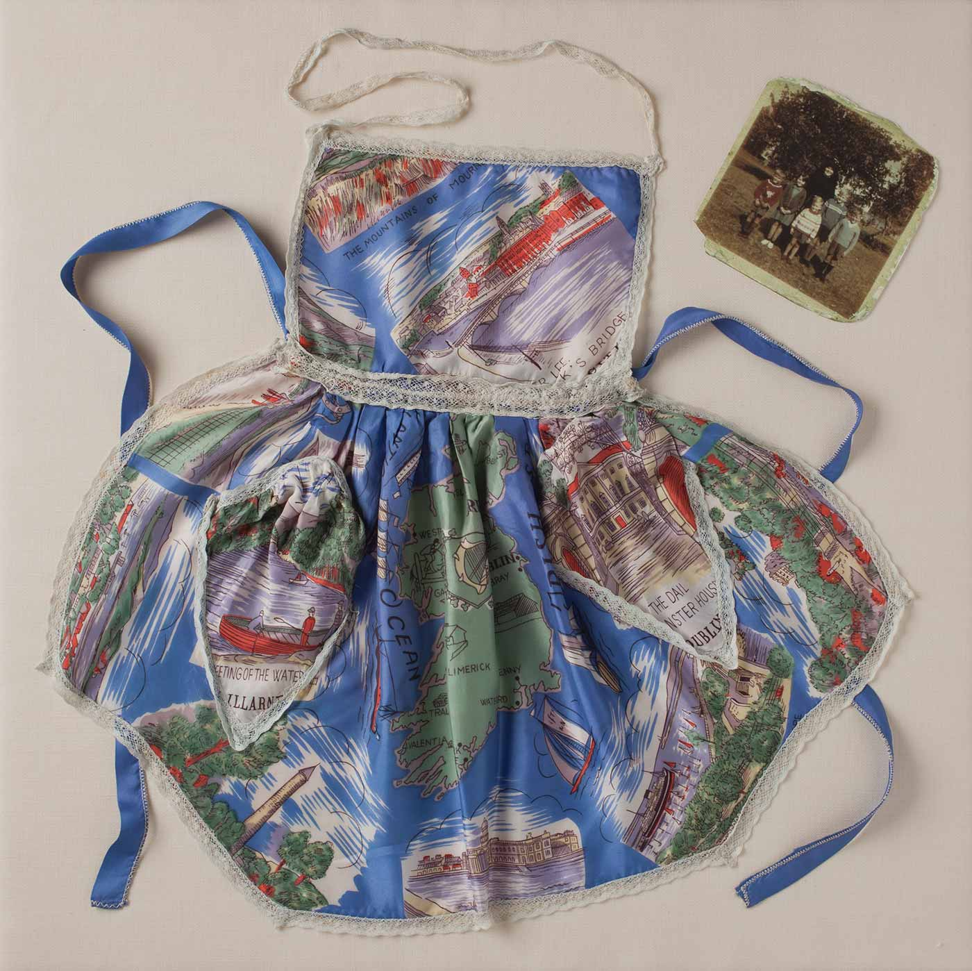 Child's apron in a silk fabric printed with a map of Ireland and sketched scenes of Irish landmarks and landscapes. - click to view larger image