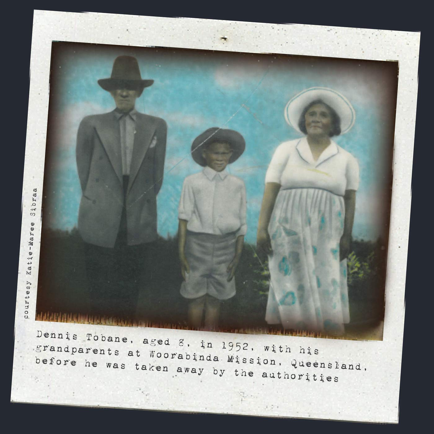 A black and white Polaroid photograph portraying three people in a standing position. From left to right, there is an elderly man wearing dark trousers with a light grey blazer, shirt and hat; a young boy who has his hands firmly by his side - he is also wearing a hat - and an elderly woman wearing a light coloured skirt, white shirt and a white hat. Typewritten text underneath reads: 'Dennis Tobane, aged 8, in 1952, with his grandparents at Woorabinda Mission, Queensland, before he was taken away by the authorities'. In smaller text, on the left-hand side of the image, in a vertical direction, reads: 'Courtesy Katie-Maree Sibraa.' - click to view larger image