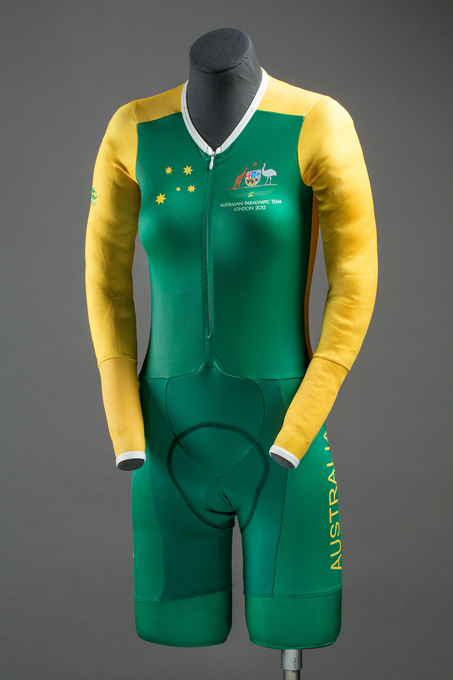 A green and yellow speedsuit with a zip half way down the front. On the front, top, right side of the speedsuit are five yellow stars and on the front, top, left side is a Australian coat of arms with the text 'AUSTRALIAN PARALYMIC TEAM / LONDON 2012' beneath it. Down the left leg of the speedsuit is the text 'AUSTRALIA' which is yellow in colour.  - click to view larger image