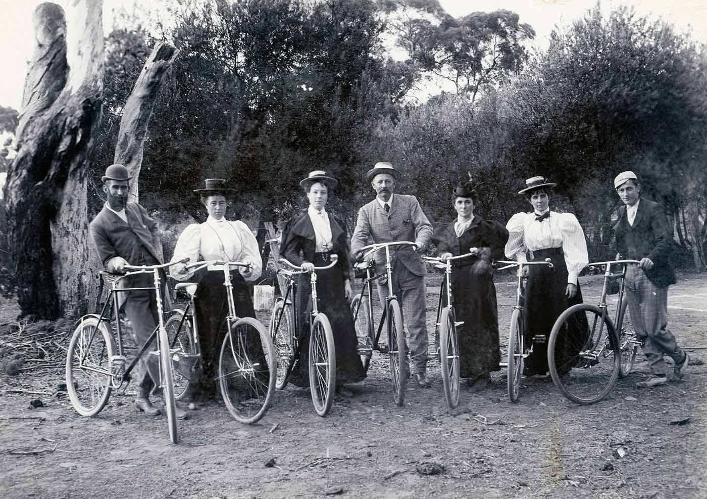 A black and white photo of a group of men and women standing with their bicycles. - click to view larger image