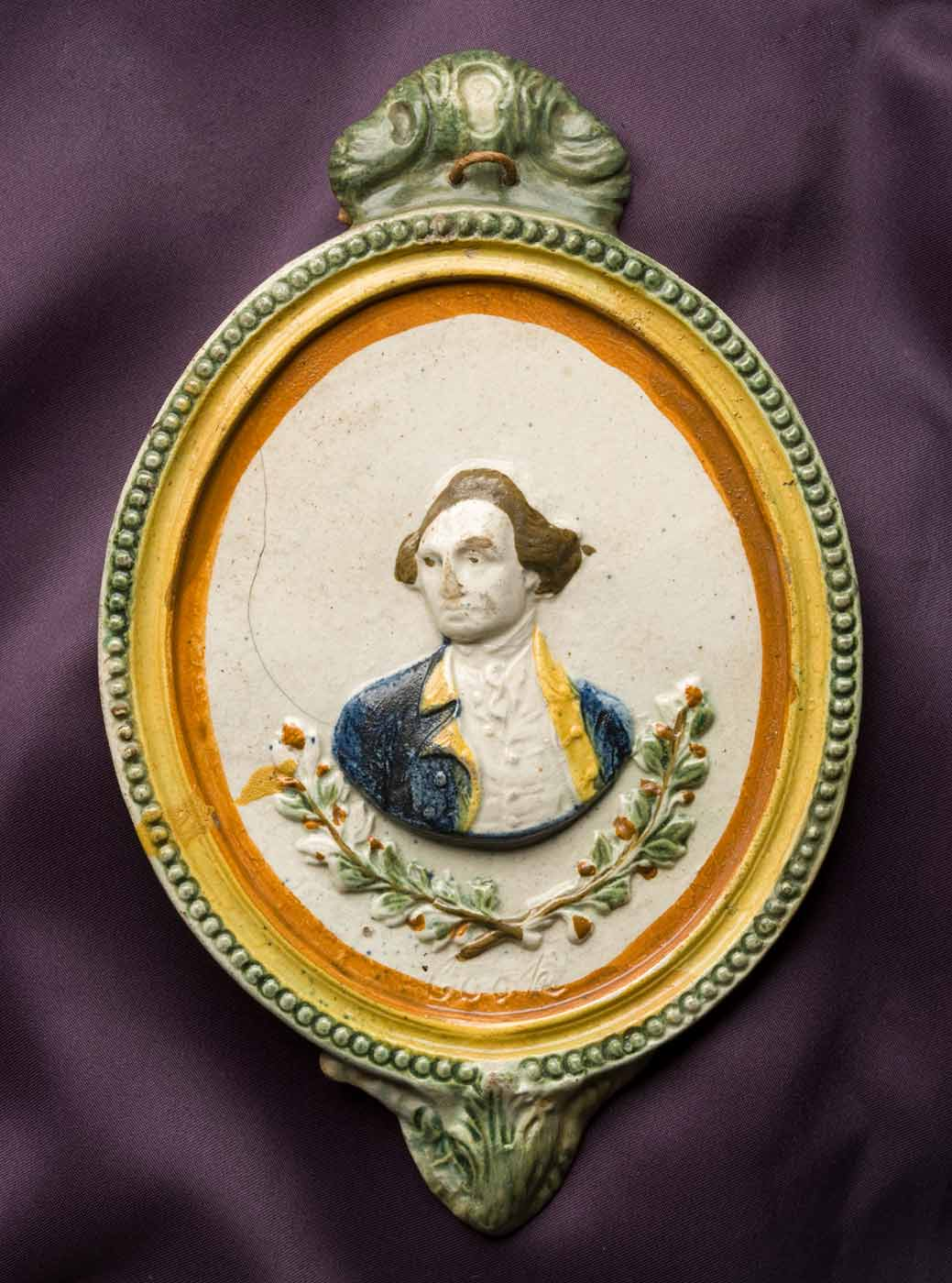A cream coloured ceramic plaque with a relief portrait bust of a man set within an open wreath. The border of the plaque is hand-painted in concentric rings of green, yellow and brown. The figure wears a blue jacket with yellow facings and a brown wig. 'Cook' is impressed in the plaque below the wreath. A piece of brown string is tied through two small holes in the foliate moulding on the top, and a similar but smaller moulding is at the bottom. A crack runs from the edge of the proper right shoulder of the plaque to the right shoulder of the figure. - click to view larger image