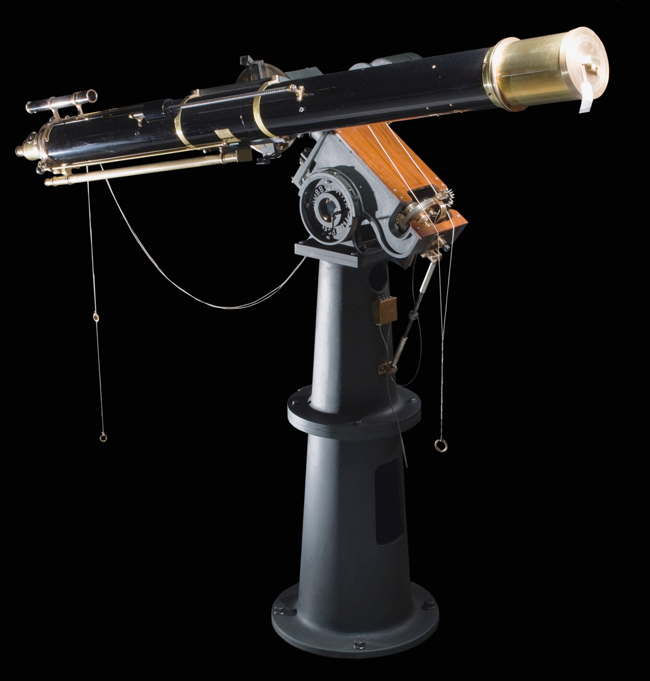 1883 Grubb Refractor Telescope made from brass. The telescope has a tapering cast iron base in two parts. The Polar Axis Assembly is made from cast iron and brass, and comes with three separate disc weights. The Declination Access Assembly is made from cast iron and steel and comes with a cylindrical weight with a pulley on the top. - click to view larger image