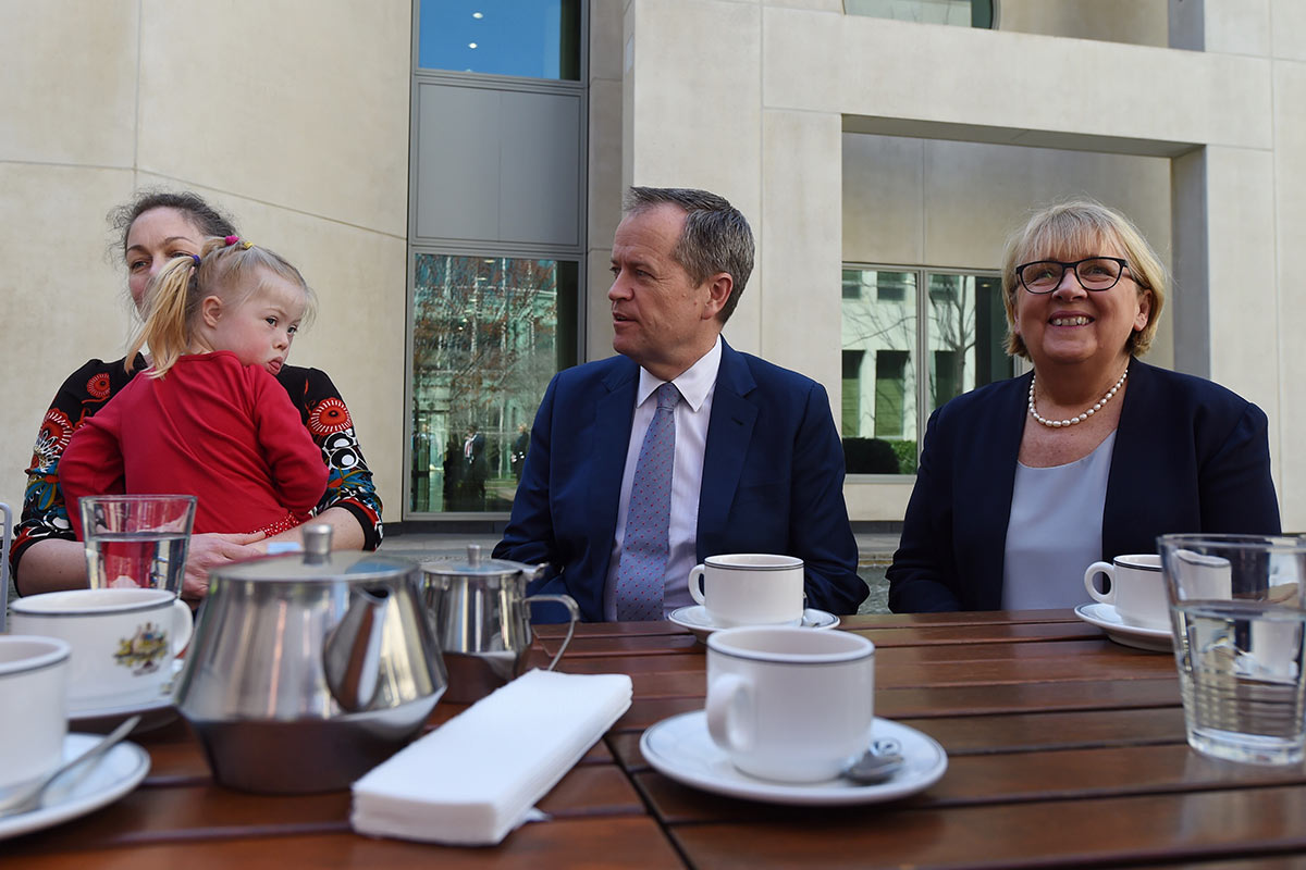 Bill Shorten and two women, one holding a young girl, are seated at a table laden with refreshments.