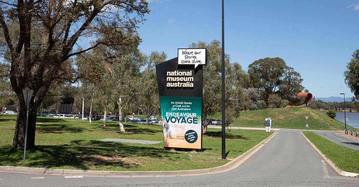 Entrance to the National Museum of Australia carpark with a large sign on the left advertising a major exhibition.