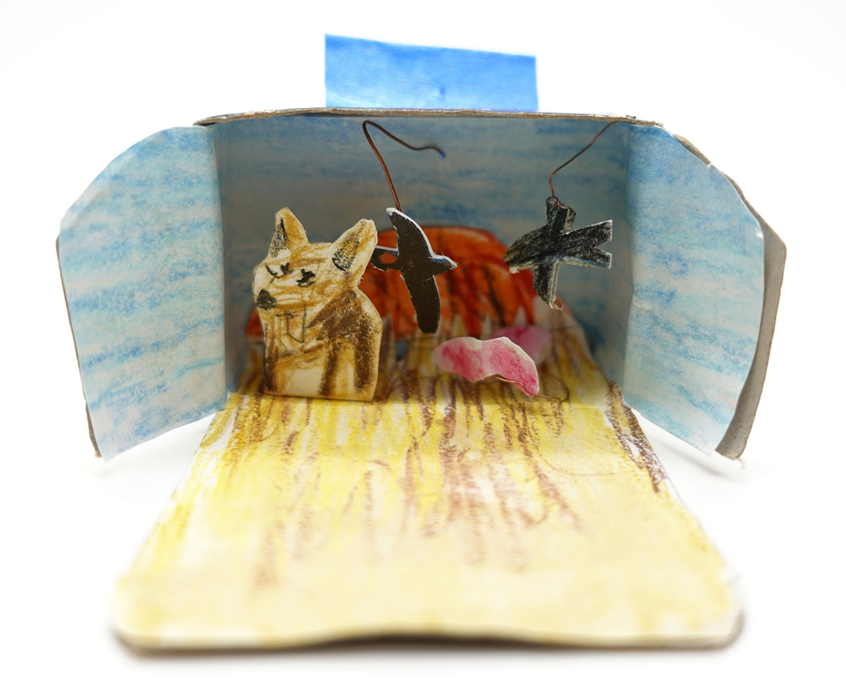 A cardboard box revealing an interior featuring a dingo and black birds against a backdrop of Uluru. - click to view larger image