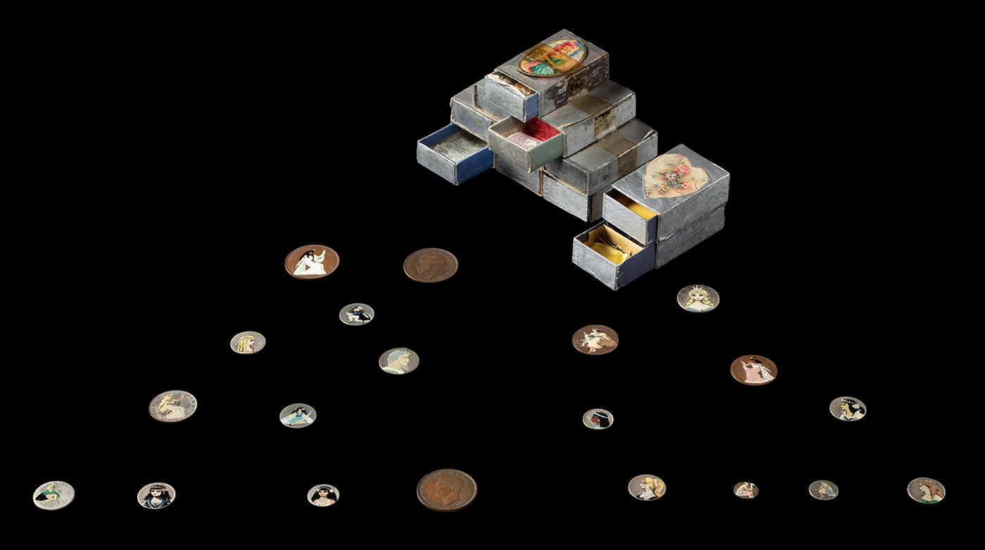 Collection of antique coins with hand-painted images on their surfaces, and adjacent to a stack of decorated matchboxes on display.