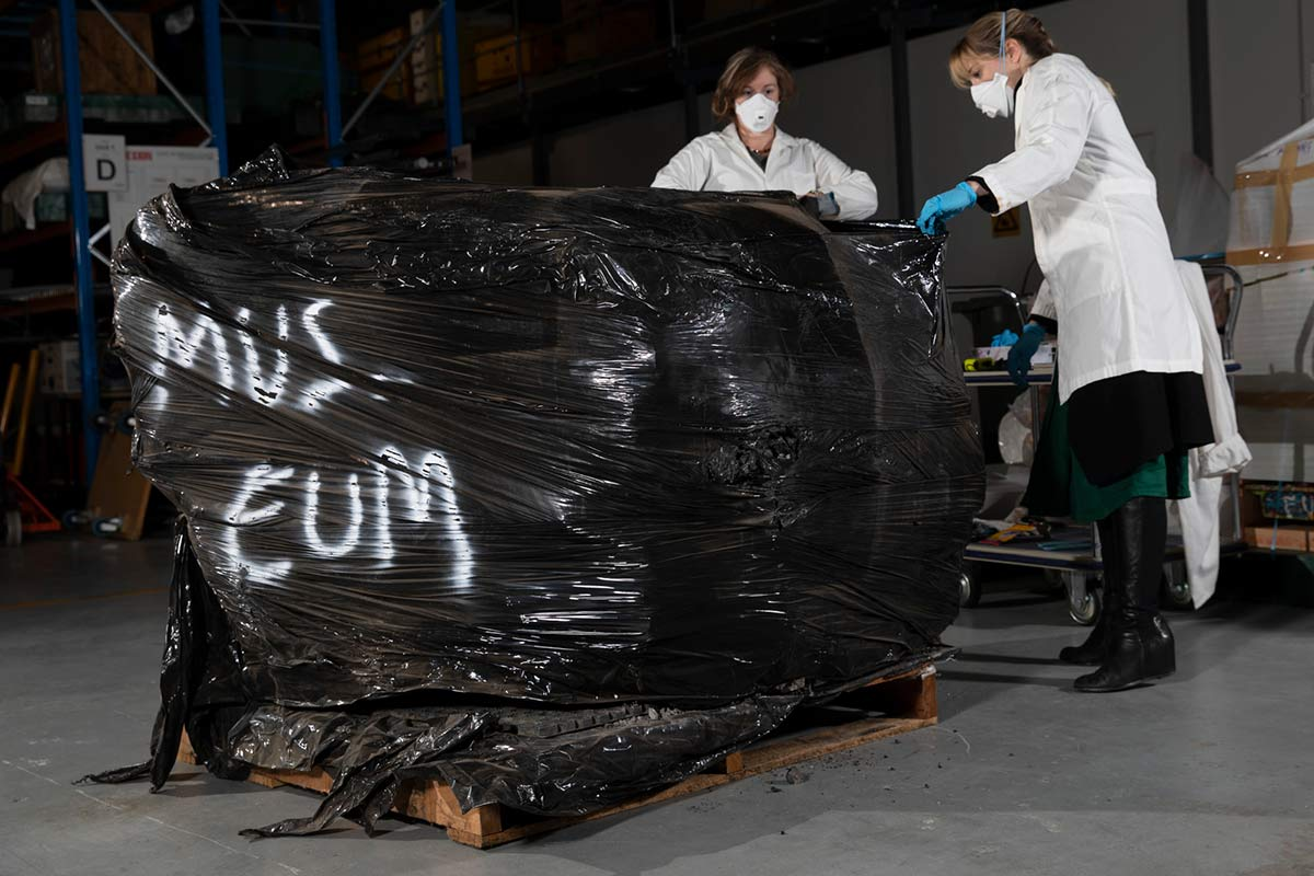 Two masked people handling a large object wrapped in plastic.