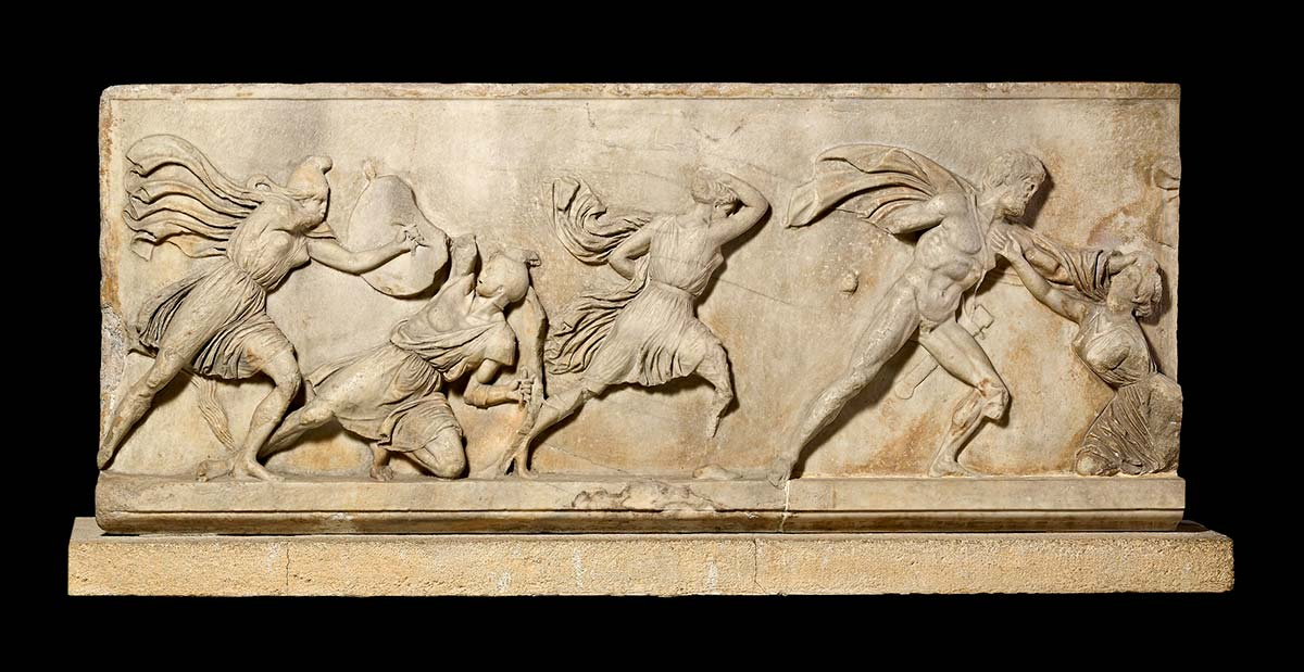 A marble block with a relief design featuring a battle scene. - click to view larger image