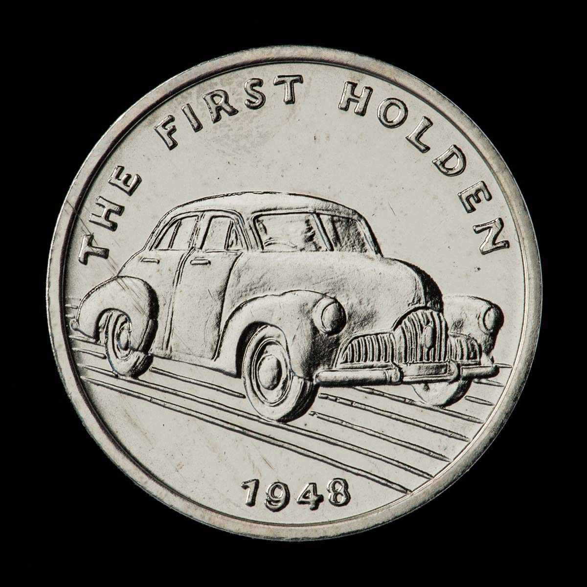 A silver coloured metal commemorative medal depicting the first Holden car. The front of the medal contains a depiction of a Holden car with the text