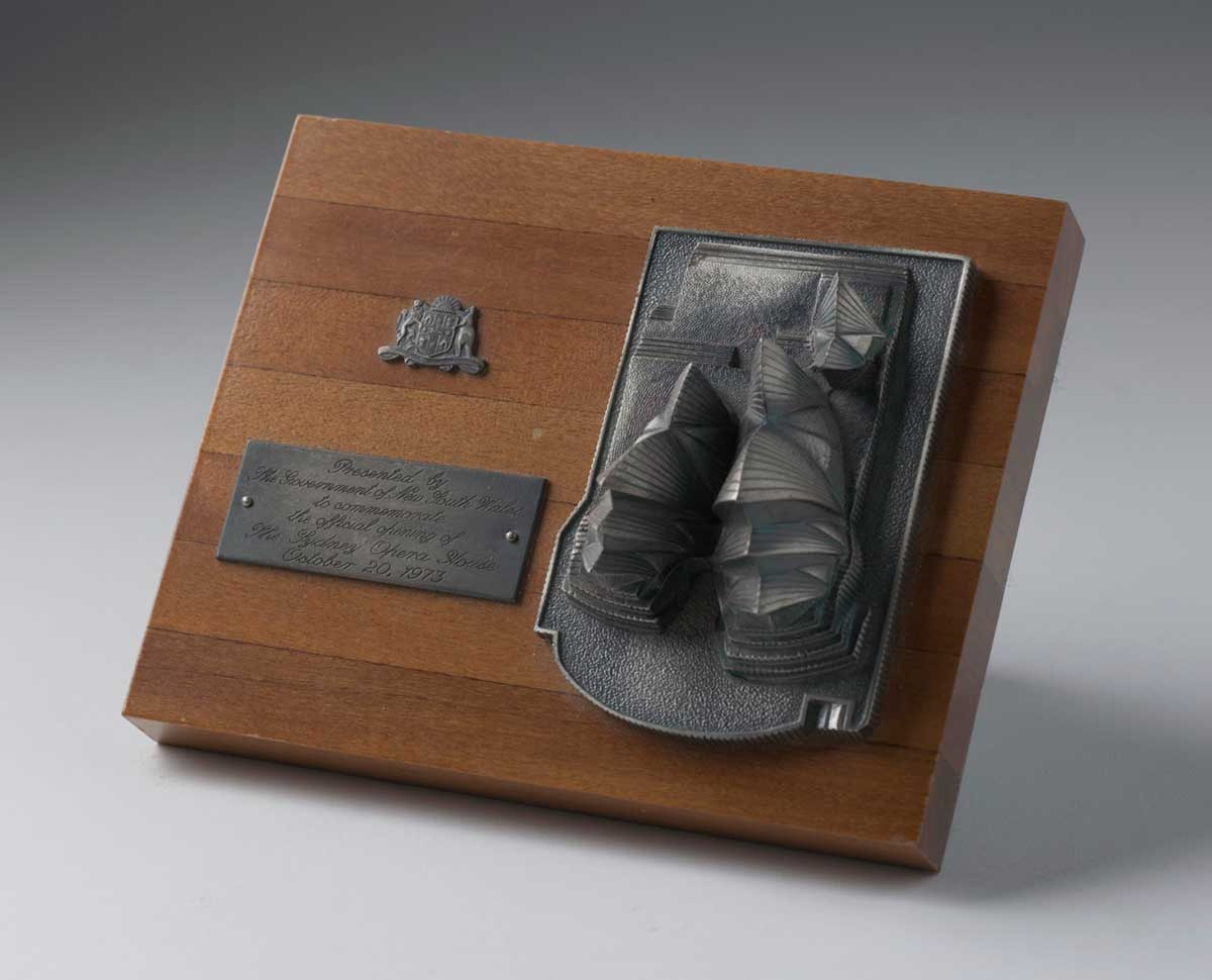 Metal (silver) miniature copy of the Sydney Opera House on a polished wooden base, with NSW emblem and plaque inscribed with the text