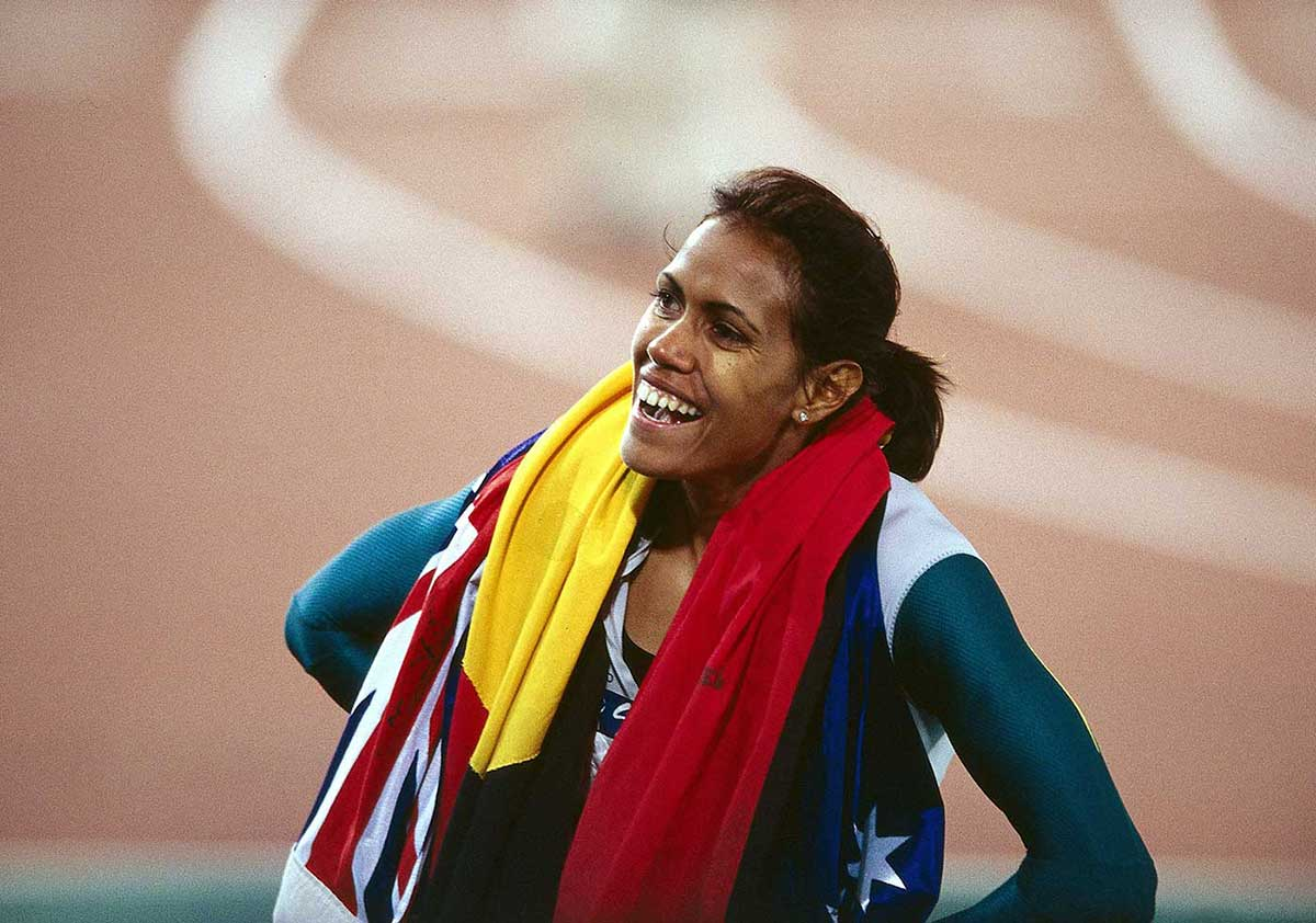 Cathy Freeman on the race track draped in the Australian and Aboriginal flags. - click to view larger image