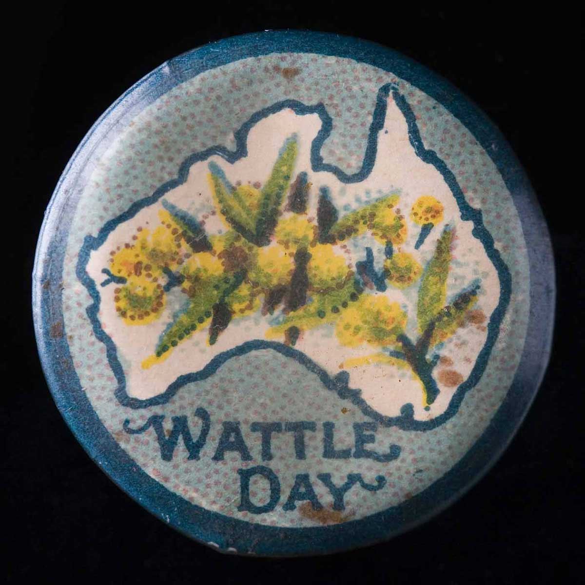 Circular badge with a blue border and background and the words 'Wattle Day' written underneath the outline of a map of Australia. Yellow wattle blossoms appear inside the map. - click to view larger image
