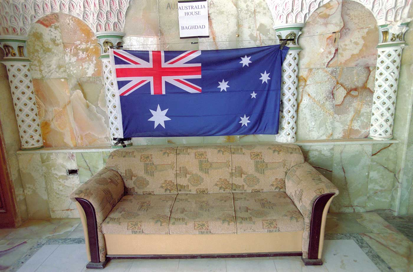 A colour photograph of the Australian flag hanging above a three-seater lounge chair. Marble-look panels and ornate columns can be seen either side of the flag. A small printed sign'Australia House, Baghdad', sits above the flag. - click to view larger image