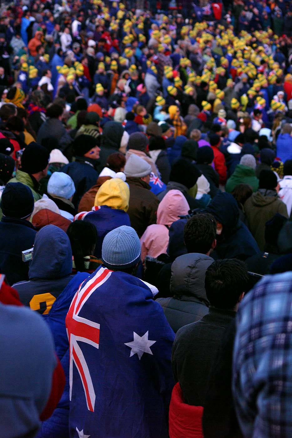 A colour photograph of a large crowd. Many people are wearing green and gold beanies on their head and several have an Australian flag draped around their shoulders. - click to view larger image
