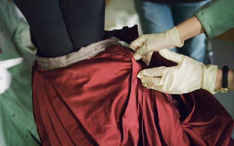 A close-up of two glove-encased hands emerging from the right side of the image holding ruby red fabric with a satiny finish. In the background and out of focus, the legs of another person are visible.