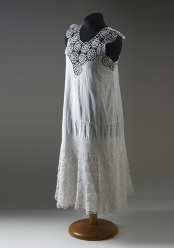 A white, cotton, sleeveless nightdress. The yoke of the nightdress is made from medallion crochet featuring a flower motif. The body of the nightdress is decorated with drawn thread work and the hem features a scalloped edge. A panel of crochet has been placed around the lower part of the nightdress.