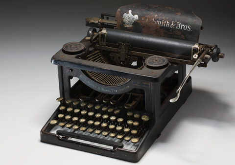 Black painted steel-framed typewriter with circular keys
