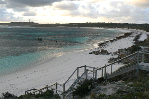 Crescent-shaped beach and bay, with wooden stairs in the foreground