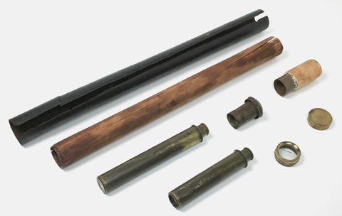 A telescope, set out in parts on a surface. All of the parts are arranged diagonally across the image, from top right to bottom left. The uppermost part is the dark leather case, split open along its length. Under it is the wooden telescope sleeve. The ends of the sleeve are cracked and the surface is mottled with dark and light areas. Under the sleeve are metal cylindrical sections, one long and two short. The short section at the right has a lght coloured outer layer, wooden in appearance. Under those sections are three more components. One is a cylinder containing a lense, one is a metal ring eyepiece and the other is a lense cap.
