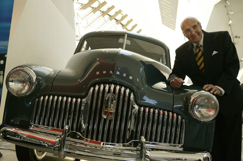 Jack Rawnsley leans on the front righthand side bonnet of a dark blue Holden. The silver grille and headlamps are prominent. The Museum's Hall forms a backdrop.