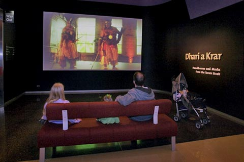 Visitors in the Dhari a Krar display watching a film of Torres Strait Islander dancers