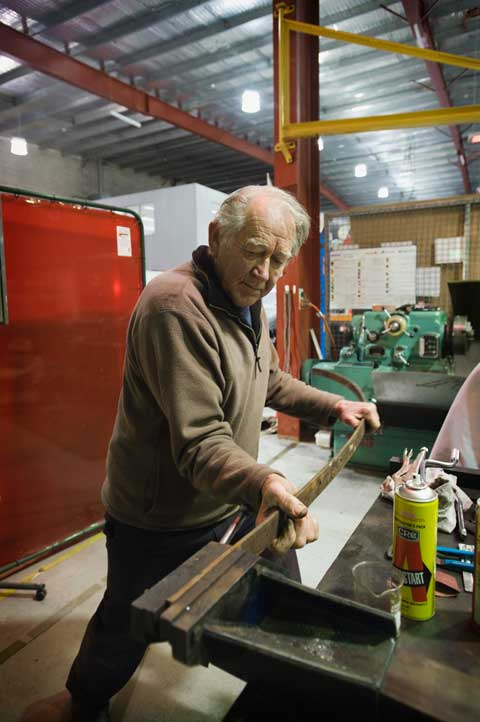 A man moves his weight towards a long, narrow strip of metal which is held in place at one end by a vice.