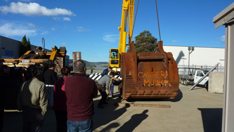 A view of a large mining excavator bucket being lifted off a semi-trailer. The bucket hangs a few centimetres off the ground, with the back of it facing the camera. Beyond the bucket can be seen the large yellow crane that has lifted the bucket off the semi-trailer. In the left foreground of the image stand two men and a woman, with their backs to the camera. In the middle of the image two men can be seen preparing to place large pieces of timber under the bucket. In the right background can be seen part of what appears to be a large white industrial shed. At the far left of the image can be seen part of some other mining equipment which is on the semi-trailer. Part of the sky is visible beyond the activity in the foreground. A few clouds are visible in the far left background.