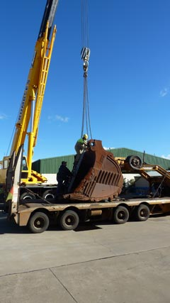 A view of a large mining excavator bucket being prepared for lifting off a semi-trailer. At the left-hand side of the image is a large yellow crane, facing the semi-trailer. The bucket faces the rear of the semi-trailer, which is at the left-hand side of the image. A man has climbed up a ladder positioned at the front of the bucket and is attaching chains from the crane. A second man is at the base of the ladder, steadying it for the other man.