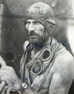 Black and white image showing a bearded and bare-chested man gazing to the left of frame. He wears a leather flying-style cap and has goggles draped around his neck. His right arm clutches a rope.