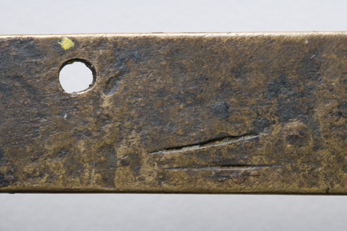 Close up image of a section of the back of the Leichhardt nameplate detailing the two score marks at the bottom close to the centre and the fastening hole at the top in the centre.