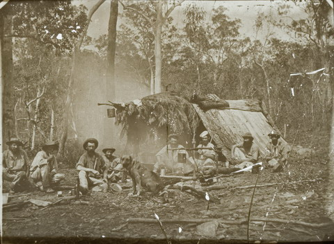 Black and white glass plate negative showing eight men sitting in front of a shelter in the bush. The A-frame shelter is made of bark and leaves and has a billy can hanging at the front. The men are gathered around a smoking fire, with another billy can hanging over the it. A dog sits at the front and centre of the image.