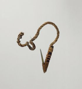 Fishhook with shank made of black wood, fish bone point, with short, twisted cord, and lashing made of plant material.