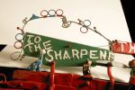 A colour photograph of a decorative detail on the Saw Doctor's wagon featuring two small animal figurines.  Part of a sign which has the letters  'TO THE SHARPENE' visible.