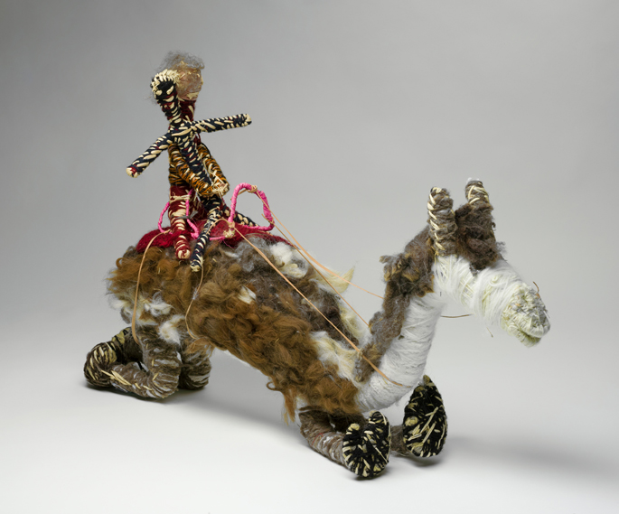 A white, grey and brown model camel with two riders made from, raffia, minarri (greybeard) grass, wool and leather. The two riders are seated on a red crocheted saddle, which is fastened to the camel with leather straps and leads.