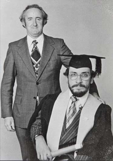 Black and white photo showing a seated man wearing academic gown and hat. A man in s suit stands to his left.