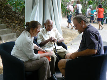 Three people sitting in an outdoor setting talking to each other.