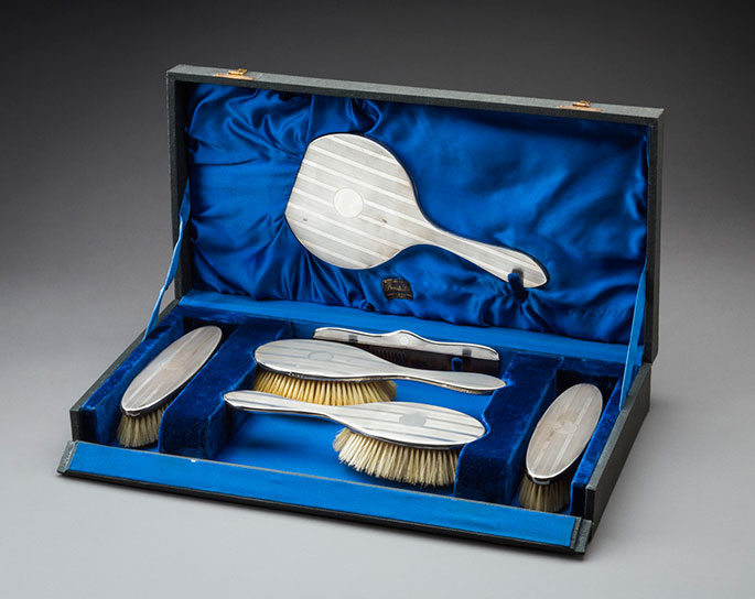 Dressing case open showing mirror, brushes and a comb