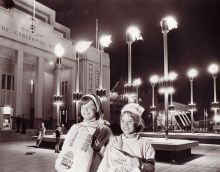Black and white photo showing two girls posing with show bags outside the Centennial Hall at night.