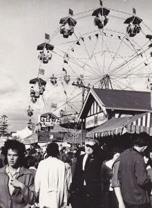 Black and white photo showing a ferris wheel in the distance and a group of people walking down sideshow alley in the foreground.