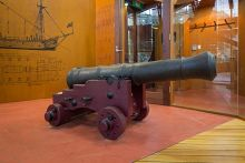 A large cannon mounted on a timber base, on display in a museum.