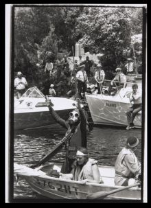 A man wearing a gas mask standing in a boat on a river. Police are observing the scene.