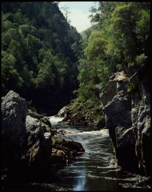 Colour photograph showing a river making its way through a high-walled rocky gorge. Lush green vegetation grows from either side of the gorge.